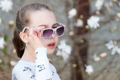 小女孩在春天夏天自然投入了太阳镜 免版税库存图片