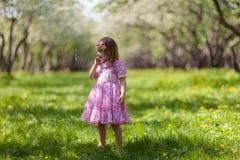 小女孩在春天庭院里 免版税库存照片