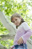 小女孩在有一张严肃的面孔的公园 免版税库存图片
