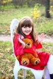 小女孩在有玩具熊的森林里 图库摄影