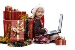 小女孩在有膝上型计算机和圣诞节礼物的圣诞老人盖帽 免版税图库摄影