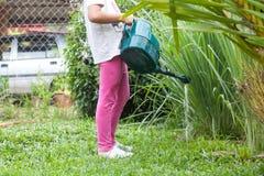 小女孩在有绿色喷壶的一个庭院里 图库摄影