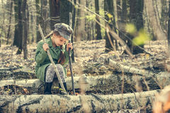 小女孩在森林坐树桩 免版税图库摄影