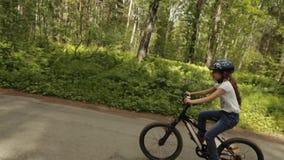 小女孩在森林足迹骑她的自行车 影视素材