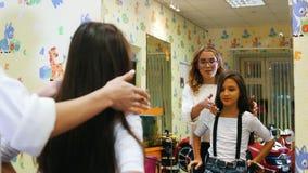 小女孩在椅子和谈话走向美发师并且记下了与美发师 影视素材