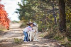 小女孩在步行的秋天公园与一条美丽的狗 免版税库存图片
