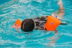 小女孩在水池游泳在一个夏日之前 库存图片