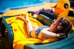 小女孩在水池附近sunbed的晒日光浴在手段 免版税图库摄影