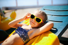 小女孩在水池附近sunbed的晒日光浴在手段 免版税库存图片