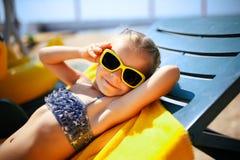 小女孩在水池附近sunbed的晒日光浴在手段 免版税库存照片