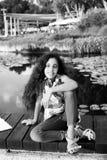小女孩在池塘附近坐一个温暖和晴朗的夏日 图库摄影
