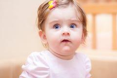 小女孩在沙发附近在家站立 免版税图库摄影
