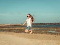 小女孩在海滩跳 免版税库存图片