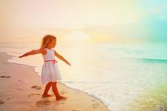 小女孩在热带海滩的戏剧飞行在日落 免版税库存图片