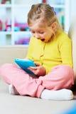 小女孩在片剂的比赛戏剧 免版税库存图片