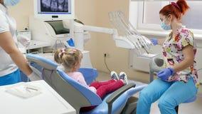 小女孩在牙齿椅子走向好医生在医院用现代设备并且坐 股票录像