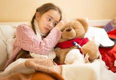 小女孩在玩具熊头和测量的temperat的举行手 图库摄影