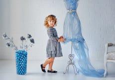 小女孩在白色背景墙壁上的一个时装模特附近站立 库存照片