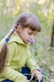 小女孩在秋天嗅一朵花 免版税库存照片