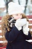 小女孩在积雪的公园加热了热的咖啡冷淡的冬天 免版税库存照片