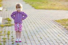 小女孩在站立用在臀部的手的夏日 免版税库存图片