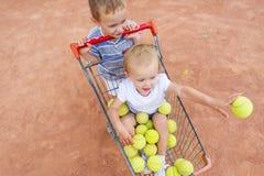 小女孩在网球的一个篮子坐 小儿童游戏在网球场 在视图之上 图库摄影
