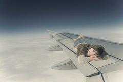 小女孩在航空器的翼说谎 库存图片