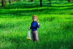 小女孩在花花圈的绿草站立  免版税图库摄影