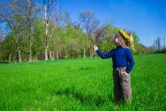 小女孩在花花圈的绿草站立  免版税库存图片