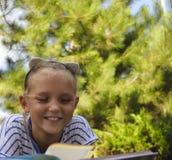 小女孩在草坪读一本书 免版税库存图片