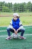 小女孩在蓝色牛仔裤和无袖的夹克穿戴了坐足球在门附近 免版税库存图片