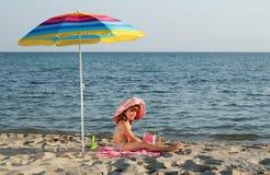 小女孩在遮光罩下坐海滩 图库摄影