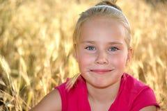 小女孩在金草坐一个夏天 库存照片