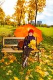 小女孩在长凳的伞下 免版税库存照片