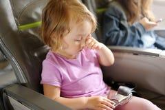 小女孩在飞机的乘客椅子坐 免版税库存照片