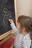 小女孩在黑板的绘画花 图库摄影