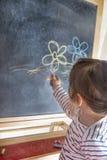 小女孩在黑板的绘画花 库存照片