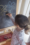 小女孩在黑板的绘画花 免版税图库摄影