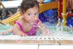 小女孩在水池的水公园。 免版税图库摄影