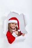 小女孩在给thums的圣诞老人成套装备上升标志 免版税图库摄影