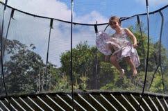 小女孩在trampolin跳 免版税库存照片