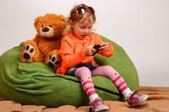 小女孩坐一个高绿色枕头和戏剧与流动酸碱度 免版税库存图片