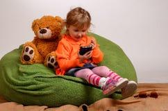 小女孩坐一个高绿色枕头和戏剧与流动酸碱度 免版税图库摄影