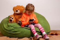 小女孩坐一个高绿色枕头和戏剧与流动酸碱度 库存图片
