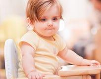 小女孩坐一把木椅子 免版税库存照片