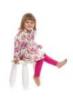小女孩坐一把椅子在演播室 库存图片