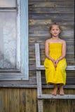 小女孩坐一架木梯子在村庄房子附近 库存图片