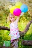 小女孩坐一棵树的分支与气球的 免版税库存图片
