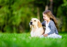 小女孩坐与狗的草 免版税库存图片
