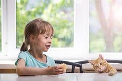 小女孩坐在与一只红色小猫,自由空间的桌上 免版税库存照片